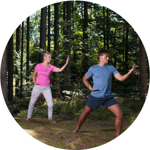 A man and a woman practicing balance in the woods